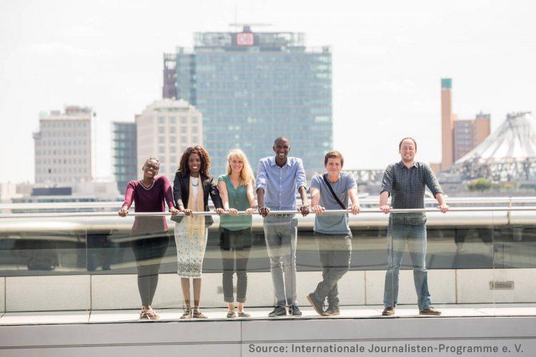 Junge Männer und Frauen vor einem Großstadthintergrund