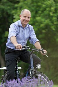 Peter Burauel mit dem Fahrrad unterwegs auf dem Campus.